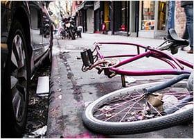 Broken bike next to a car