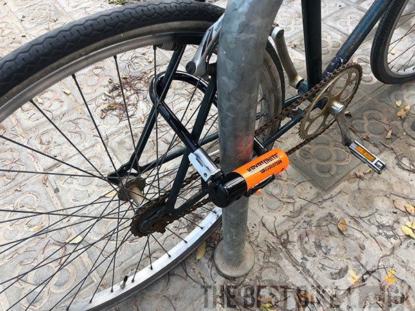 A bike locked through the seat stays and spokes